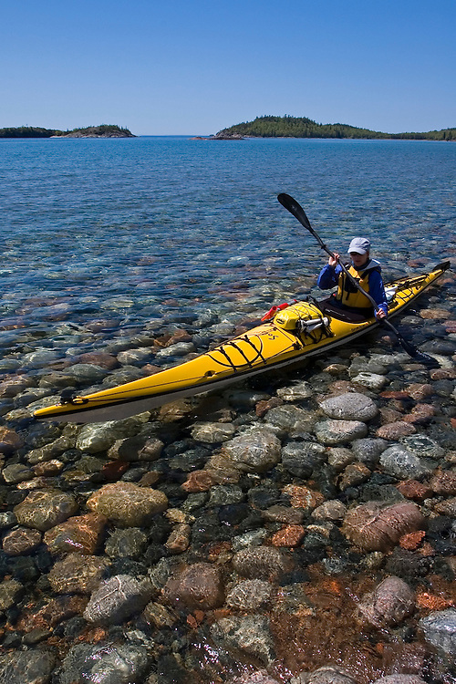 A sea kayaker floats over cobblestones in the clear water of Gargantua Harbor in Lake Superior Provincial Park near Wawa Ontario Canada.