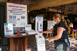 © Licensed to London News Pictures. 26/10/2020. London, UK. A woman wearing a face covering uses a hand sanitiser in a Wetherspoons pub in north London. The hospitality industry estimates that pubs, bars and restaurants have spent £900million on screens, masks and hand sanitisers to make their venues safe for reopening, following the easing of COVID-19 lockdown restrictions. It has been reported that each pub has spent more than £10,000 adapting the interiors of their venues but with the latest restrictions, many now only serve customers outside their premises. Wetherspoons has spent £13.1million on getting its 875 pubs ready. Photo credit: Dinendra Haria/LNP
