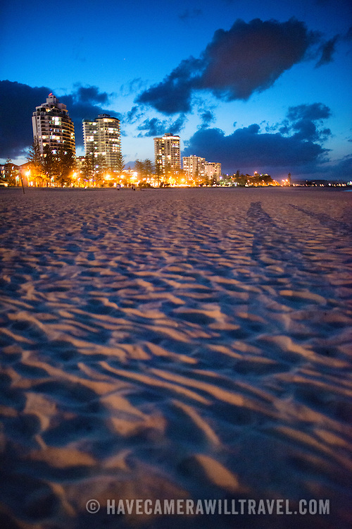 """Coolangatta's beach and skyline at dusk. Sometimes paired as """"Twin Towns,"""" Coolangatta and Tweed Heads, on the southern end of the Gold Coast, straddle the Queensland-New South Wales border."""