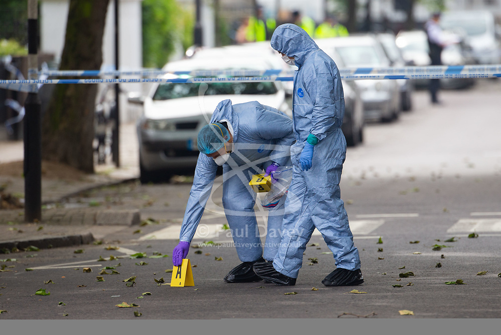 Forensics investigators place markers at the scene outside a block of flats at 65 Finborough Road, adjoining Cathcart Road, Chelsea following the fatal stabbing on the night of May 30th 2018 of a man in his forties, said to be a delivery driver who refused to hand over his cash to robbers. London, May 31 2018.