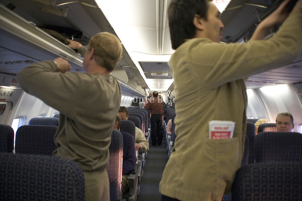 passengers stowing there carryon luggage away inside an airplane