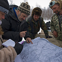 Gretel Ehrlich, guide Andrei Volkov, Komi clan leader Vasily Terentev and other nomadic reindeer herders examine a map of where the group will be traveling while journalists are with their group.