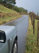 A car driving along a rain washed country road in the hills near San Sebastian, Spain