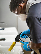 """19 MARCH 2020 - DES MOINES, IOWA: DANIEL BROWN, a worker for Des Moines Public Schools, sanitizes and disinfects a boys' bathroom at Central Campus, a high school in the Des Moines Public Schools system. Des Moines schools are closed for at least 30 days because of the coronavirus and officials are using the time to """"deep clean"""" and sanitize each school. On Thursday morning, 19 March, Iowa reported 38 confirmed cases of the Coronavirus. Restaurants, bars, movie theaters, places that draw crowds are closed for at least 30 days. There are no """"shelter in place"""" orders in effect anywhere in Iowa but people are being encouraged to practice """"social distancing"""" and many businesses are requiring or encouraging employees to telecommute.          PHOTO BY JACK KURTZ"""