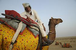 Camel riders pose the SAM dunes near Jaisalmer in India's Rajasthan Thar desert. (Photo by Ami Vitale)..Riders:.Chotu Ram (reddish brown shirt).Gopu Ram (pink shirt).Ashok Ram (blue striped shirt)