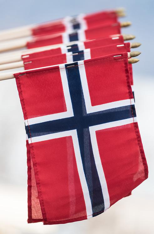 En lang rekke hengende, norske flagg med himmelen som bakgrunn.