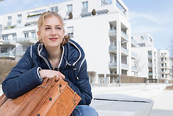 Young woman waiting with city in background, Munich, Bavaria, Germany