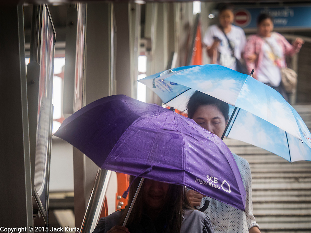 """16 SEPTEMBER 2015 - BANGKOK, THAILAND:  People with umbrellas leave the Phaya Thai BTS Station in Bangkok during a rainstorm. The remnants of tropical storm """"Vamco"""" hit Bangkok Wednesday. The storm, downgraded to a tropical depression, brought bands of rain to central Thailand, including Bangkok. The Thai Meteorological Department said the storm would help alleviate the drought that has gripped Thailand since late last year.     PHOTO BY JACK KURTZ"""