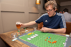 Edinburgh football fan and game designer Colin Webster has designed a brand-new football strategy game called Counter Attack. Last night he hosted a game session in Leith to demonstrate the game to a few interested players. The game is currently on the crowd-funding site Kickstarter and on track to meet it's funding target. If so, Colin hopes the gamne will be available by August this year. Pictured: Colin explains the rules of his new game<br /> <br /> <br /> © Jon Davey/ EEm