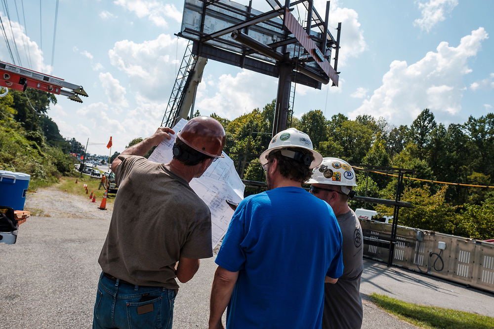 Left to right, Greg Gentry, a sub contractor working for Lamar, Dwayne Mace, Regional Technician at Lamar, center, and Robert Farthing, Operations Manager at Lamar, go over plans while technicians from Lamar Advertising install a digital billboard structure along Wards Road in Lynchburg, VA Wednesday, August 29, 2018. U.S. companies are investing in re-training efforts to fill a slew of open positions as a tight labor market and changing job requirements makes it hard to find qualified staffers.<br /> CREDIT: Justin Ide for The Wall Street Journal<br /> RETRAIN