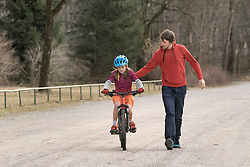 Man helping daughter with closed eyes to ride bicycle, Bavaria, Germany