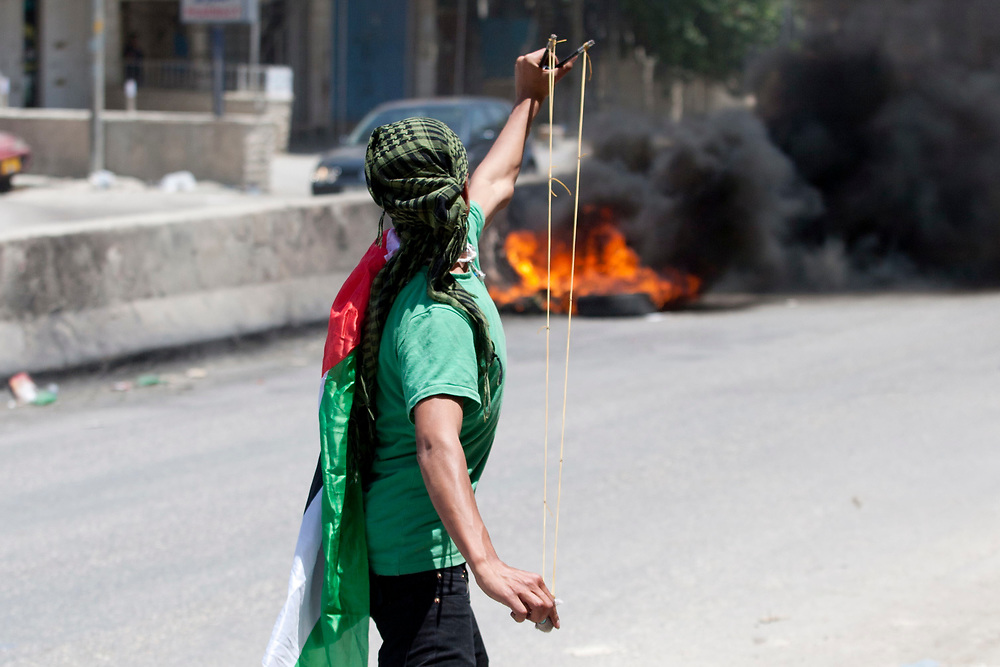 A Palestinian demonstrator draped in a Palestinian flag uses a sling-shot to hurl stones, during clashes with Israeli troops at the Qalandiya checkpoint, between Jerusalem and the West Bank city of Ramallah on June 5, 2011. Palestinians Mark The 44th Anniversary of the 1967 Six Day War.