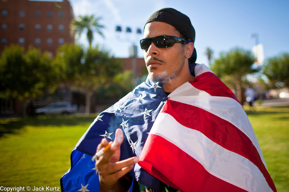 14 OCTOBER 2011 - PHOENIX, AZ:   CRAIG MERCHANT wrapped himself in the American flag before the Occupy Phoenix march. About 300 people participated in the Occupy Phoenix march through downtown Phoenix Friday evening, Oct. 14. The march was the first event in the Occupy Phoenix protests which start with the occupation of Cesar Chavez Plaza, a large square in downtown Phoenix. PHOTO BY JACK KURTZ