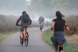 © Licensed to London News Pictures. 10/10/2018. London, UK. Runners and cyclists at sunrise on a misty morning in Bushy Park, south London. Forecasters are expecting unusually warm temperatures for October. Photo credit: Rob Pinney/LNP