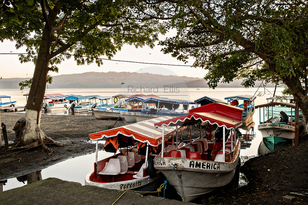 Water taxis called Pangas tied up along the shore of Lake Catemaco in Catemaco, Veracruz, Mexico.  The tropical freshwater lake at the center of the Sierra de Los Tuxtlas, is a popular tourist destination and know for free ranging monkeys, the rainforest backdrop and Mexican witches known as Brujos.