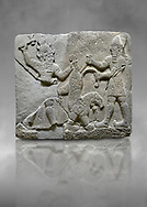 Hittite relief sculpted orthostat stone panel of Herald's Wall Basalt, Karkamıs, (Kargamıs), Carchemish (Karkemish), 900-700 B.C. Anatolian Civilisations Museum, Ankara, Turkey.<br /> <br /> On the right is a bearded human figure with a short skirt; with the dagger in his right hand, he is stabbing the lion standing on his front legs while holding the lion's tail with his left hand. On the left is a bearded god figure with a horned-headdress, who grasps the lion's hind leg while holding the ax over his head with his right hand. <br /> <br /> Against a grey art background. .<br />  <br /> If you prefer to buy from our ALAMY STOCK LIBRARY page at https://www.alamy.com/portfolio/paul-williams-funkystock/hittite-art-antiquities.html  - Type  Karkamıs in LOWER SEARCH WITHIN GALLERY box. Refine search by adding background colour, place, museum etc.<br /> <br /> Visit our HITTITE PHOTO COLLECTIONS for more photos to download or buy as wall art prints https://funkystock.photoshelter.com/gallery-collection/The-Hittites-Art-Artefacts-Antiquities-Historic-Sites-Pictures-Images-of/C0000NUBSMhSc3Oo