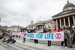 London, UK. 23rd August, 2021. Environmental activists from Extinction Rebellion hold banners in Trafalgar Square during the first day of Impossible Rebellion protests. Extinction Rebellion are calling on the UK government to cease all new fossil fuel investment with immediate effect. Credit: Mark Kerrison/Alamy Live News