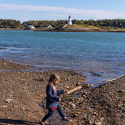 A girl explores the shoreline in Lubec, Maine. Mullholland Point Light is across Lubec Narrows on Campobello Island.
