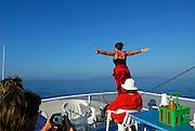 "Tourists above deck on inter-island charter boat, one striking classic ""Titanic"" pose, island of Brac in distance. Near Makarska, Croatia"