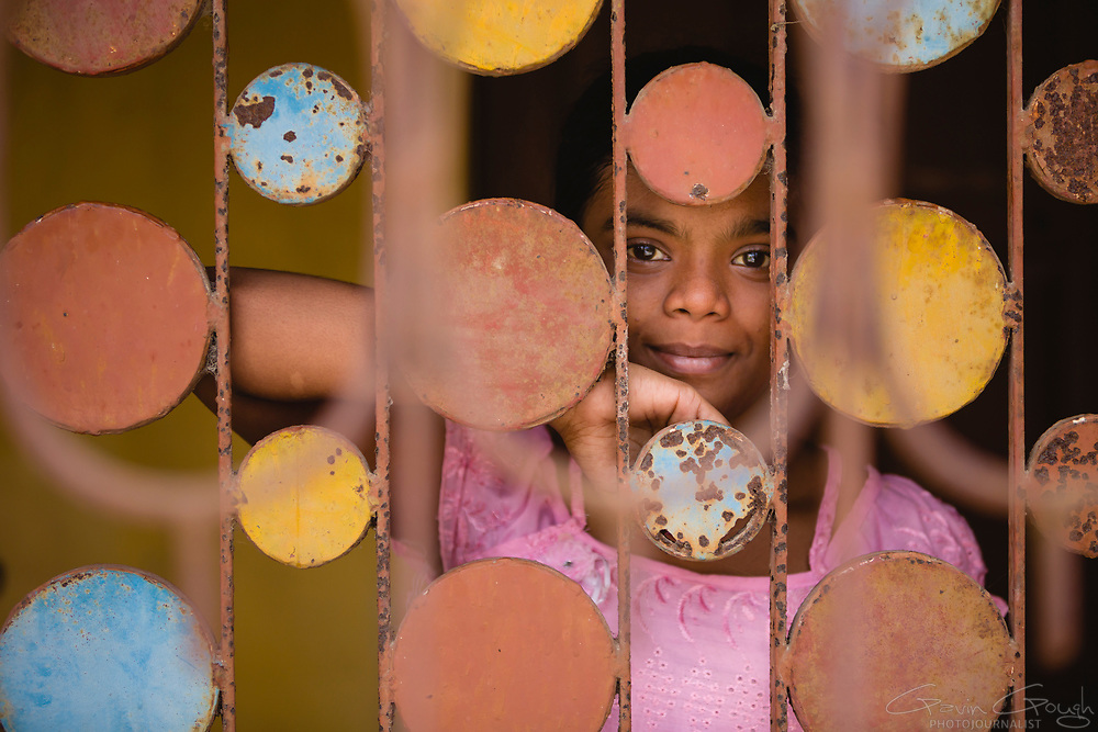 A girl posing behind decorative bars at the front door of her family home, Jote, Shibrampur, Kolkata, India
