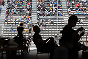 Members of the press work as spectators watch the men's cycling road individual time trial during the Tokyo 2020 Olympic Games at the Fuji International Speedway in Oyama, Shizuoka prefecture on July 28, 2021. - At the Fuji Speedway venue, around 100 kilometres (60 miles) from Tokyo, the rules on July 28 allowed for 10,000 spectators, less than half the venue's full capacity of 22,000. (Photo by Yuki IWAMURA / AFP)