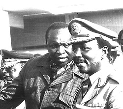 General Yakubu Gowon, who is reported to have been ousted as Nigeria's Head of Government in a military coup, talking with Uganda's President Idi Amin (left) today at the summit meeting of the Organisation of African Unity in Kampala.