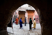 Liana Welty, an American tourist, stands still and watches as local Moroccans walk past her in a street in the Marrakech medina, Morocco on November 16, 2007.
