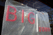 A detail red lettering, the frontage of a new restaurant business to be called 'Big Town' and offering West African food, is still covered in Bubble-Wrap during the property's conversion on the Walworth Road in south London, on 23rd August 2019, in London, England.
