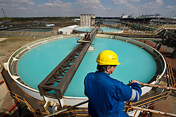 Inspector Guido De Rycke looks over brine tanks at the Solvay SA chemical plant in Antwerp, Belgium. The blue color is caused by the high concentration of salt, which is used to make chlorine, the main product of the Solvay's Antwerp facility.  Solvay SA is the world's largest supplier of Soda Ash or Sodium Carbonate and is also a major producer of caustic soda, hydrogen peroxide, chlorine and fluorinated products. (Photo © Jock Fistick)