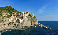 An colorful Italian fishing village clings to a cliff above the Mediterranean sea.