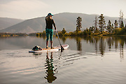 A female paddlboarder on Lake Dillon in Summit County, Colorado in the early morning.