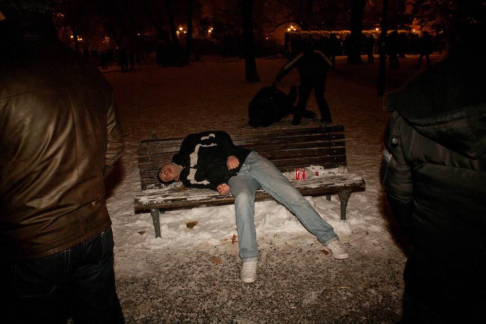 New Year's Eve (December 31) in Belgrade, Serbia. Parliament square and Pionirski Park. Man passes out on public bench after drinking too much.