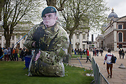 Families queue in the grounds of the Naval College, Greenwich past a giant inflatable figure of a member of Royal Marines Commandos. During a public open-day in Greenwich, London when the Royal Navy's aircraft carrier HMS Illustrious docked on the river Thames, allowing the tax-paying public to tour its decks before its decommisioning. Navy personnel helped with the PR event over the May weekend, historically the home of Britain's naval fleet.