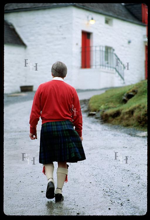 Guide in kilt walks path to the malt barn at Edradour, smallest distillery in Scotland;Pitlochry Scotland