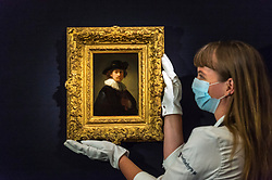 "© Licensed to London News Pictures. 23/07/2020. LONDON, UK. A technician presents ""Self-portrait, wearing a ruff and black hat (1632) by Rembrandt Van Rijn, estimate: £12-16 million. Preview of works on display at Sotheby's London ahead of a one-off auction on July 28.  Titled 'Rembrandt to Richter', the sale will offer the very best from Old Masters, Impressionist & Modern Art, Modern & Post-War British Art and Contemporary Art.  The exhibition is open to the public at Sotheby's New Bond Street galleries until July 28. [Image embargoed for release until 9am BST 24 July 2020].  Photo credit: Stephen Chung/LNP"