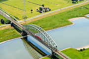 Nederland, Gelderland, Gemeente Arnhem, 26-06-2013; trein van Arriva op dubbelsporige stalen spoorbrug over de Neder-rijn. Spoorwegverbinding tussen Arnhem en  richting Nijmegen.<br /> Railway bridge over river Rhine west of Arnhem.<br /> luchtfoto (toeslag op standaard tarieven);<br /> aerial photo (additional fee required);<br /> copyright foto/photo Siebe Swart.