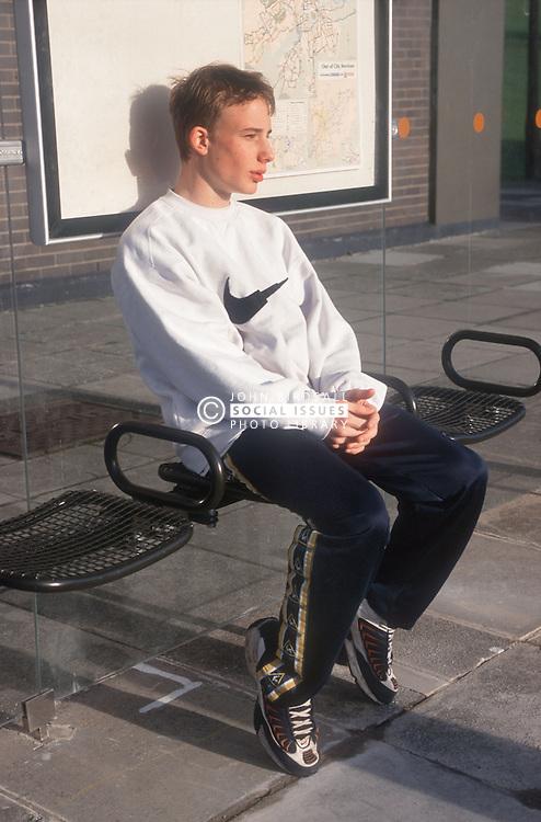 Teenage boy waiting at bus stop looking serious,