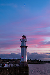 Edinburgh, Scotland, UK, 16th June 2021. Sunset at Newhaven Harbour: A crescent moon sets over the harbour just after sunset with the lighthouse lit up at dusk.<br /> Sally Anderson | EdinburghElitemedia.co.uk