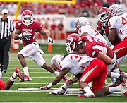Sep 10, 2011; Little Rock, AR, USA; Arkansas Razorback wide receiver Joe Adams (3) carries the ball as Arkansas Razorback offensive tackle Grant Freeman (79) makes the tackle against New Mexico Lobos safety A.J. Butler (34) and linebacker Jarrett Lake (39) during the first half at War Memorial Stadium.  Mandatory Credit: Beth Hall-US PRESSWIRE