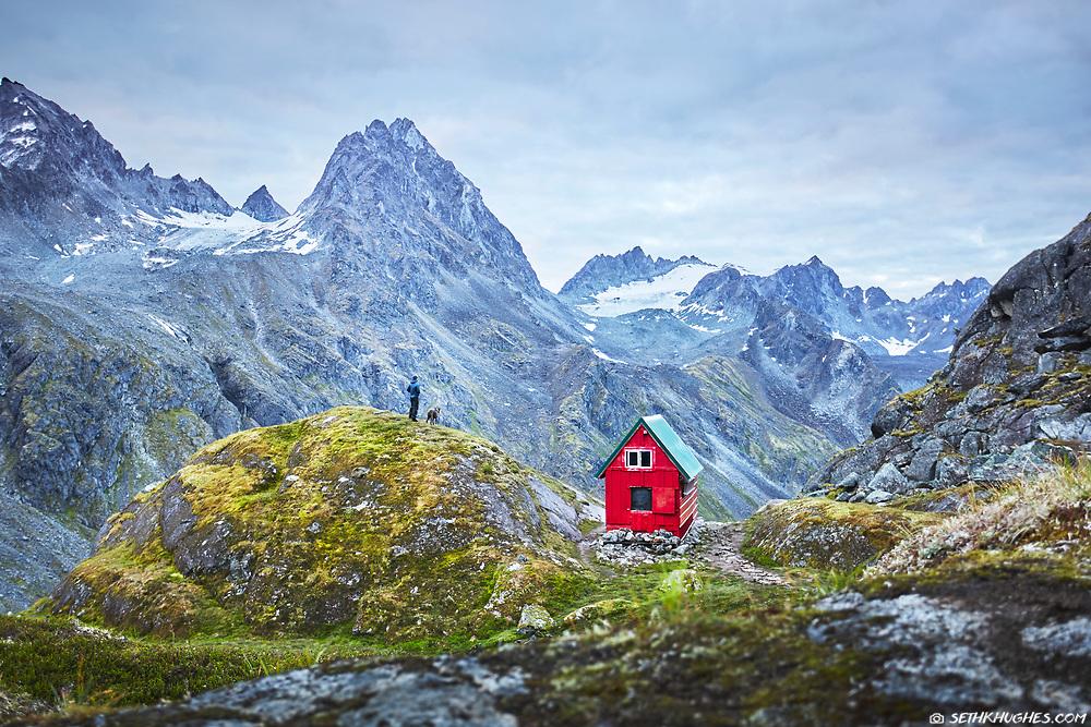 A hiker and his dog stand next to the Mint Hut overlooking the Talkeetna Mountains near Hatcher Pass, Alaska.