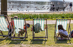 Licensed to London News Pictures. 19/04/2021. London, UK. Brae Wegg-Prosser 7 (blue sunglasses) plays hide-and-seek with his siblings and friends on deckchairs in Hyde Park London as they soak up the sunshine a week after the easing of Covid-19 restrictions as a mini heatwave hit the UK this week with temperatures reaching up to 18c in London and the South East. Photo credit: Alex Lentati/LNP<br /> <br /> *Permission granted*