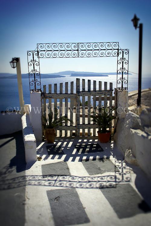 An entry gate, a wrought iron awning, the Aegean sea, Santorini, Greece