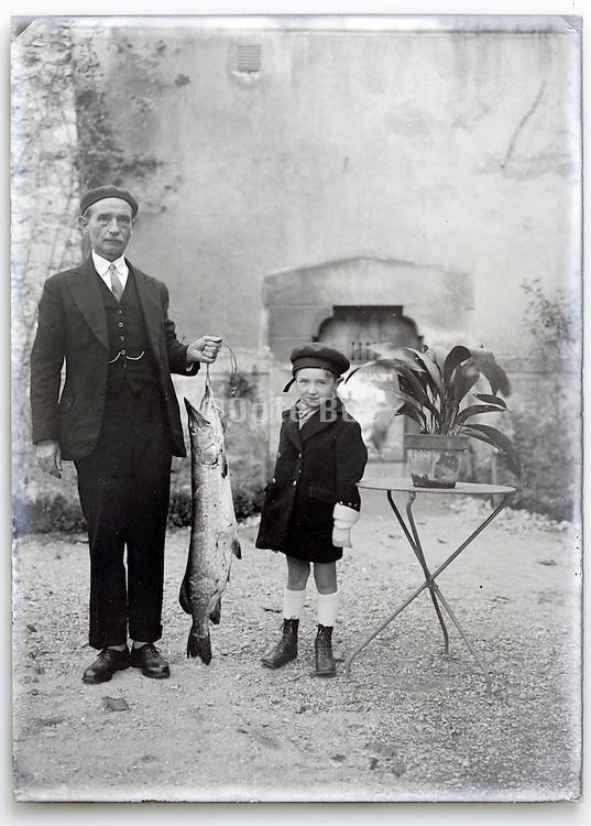 elderly man holding large fish with grandchild vintage 1900s