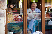 A couple read newspapers in the window of a cafe on the Rue Mouffetard.<br /> Rue Mouffetard is in the Fifth (cinquieme) arrondisement and the street is one of the oldest in Paris. A Roman road, it originally ran from the Roman Rive Gauche city all the way to Italy. Today, the market is famous for it's quality fresh produce and artisanal food shops.