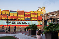Savannah, Georgia, USA - July 25, 2021: People watch the arrival of a Maersk Line ship, the MSC Ellen, as it moves up the Savannah River toward its docking point. A Starbucks is on the right of the image.