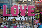A valentines Day merchandise retail window in the City of London. The word Love has been pasted on to the window in large lettering above Happy Valentines. Cheap and cheerful gifts for this romantic occasion can be seen in the background as well as a Valentine's Day balloon. Valentine's Day takings are expected to exceed £1.3bn, says the British Retail Consortium. The spending is led by generous — or panicking — men. It was estimated last year that British men would fork out £622m between them, compared to the £354m spent by women