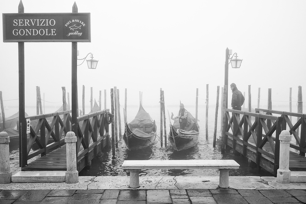 Two gondolier have a chat while Venice wakes up un in a cloud of fog