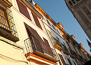 Late afternoon golden sunlight falling of historic houses in Placentines street, central Seville, Spain next to La Giralda tower