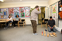 Care worker setting up indoor bowls game for a group of Day service users with learning disabilities,