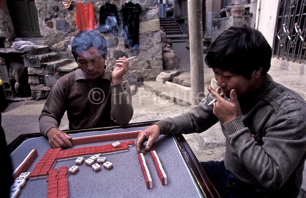 Two men play Mahjong on island of Jin Shan, China